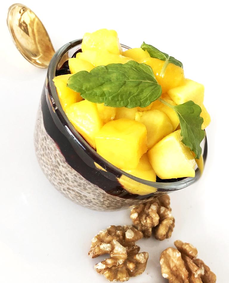 En skål med chiapudding toppad med mango, mynta och några valnötter vid sidan om.