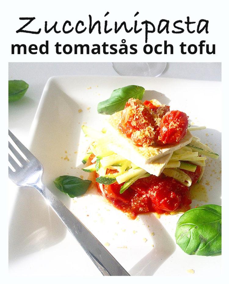Ett fat med vegansk zucchinipasta med tomatsås och tofu.