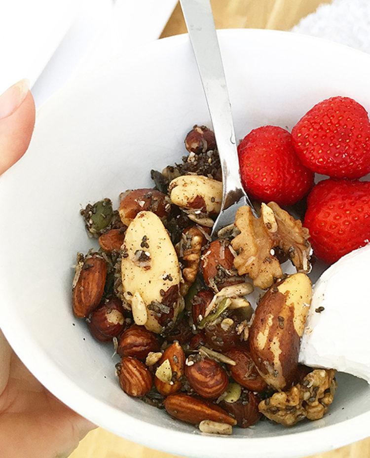 En skål med nöt granola, kokosgrädde och jordgubbar.