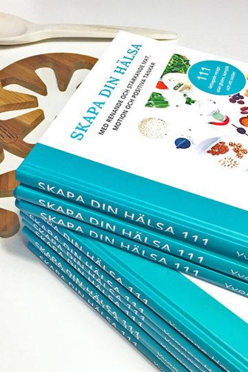 En bunt med kokboken Skapa din hälsa.