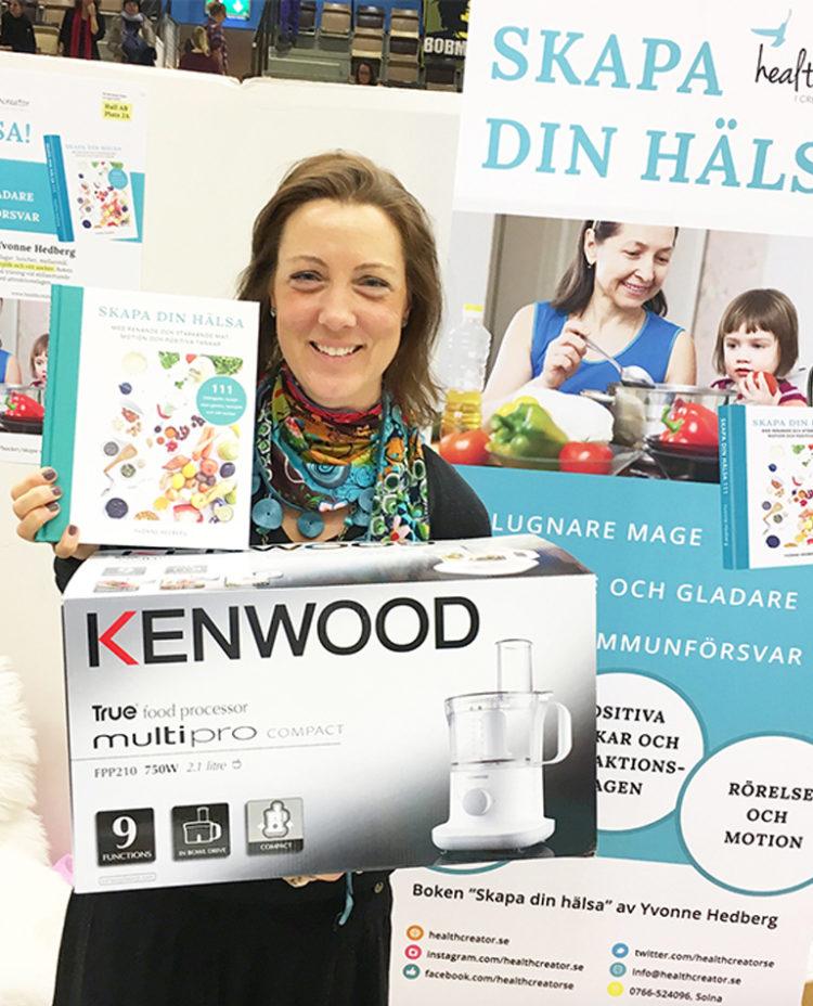 En tjej håller upp kokboken Skapa din hälsa och en matberedare hon vunnit från healthcreator på Harmoni Expo mässan.