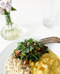 Ett fat med vegansk currygryta, ris och lättfräst grönkål står bredvid en vas med blommor.