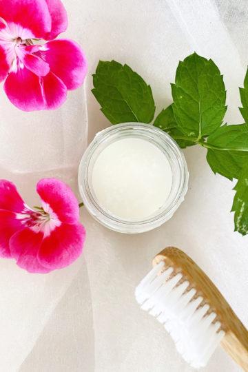 En burk med hemmagjord tandkräm bredvid rosa blommor.
