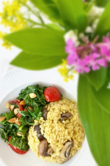 Ett fat med vegansk risotto med en bukett blommor vid sidan om.