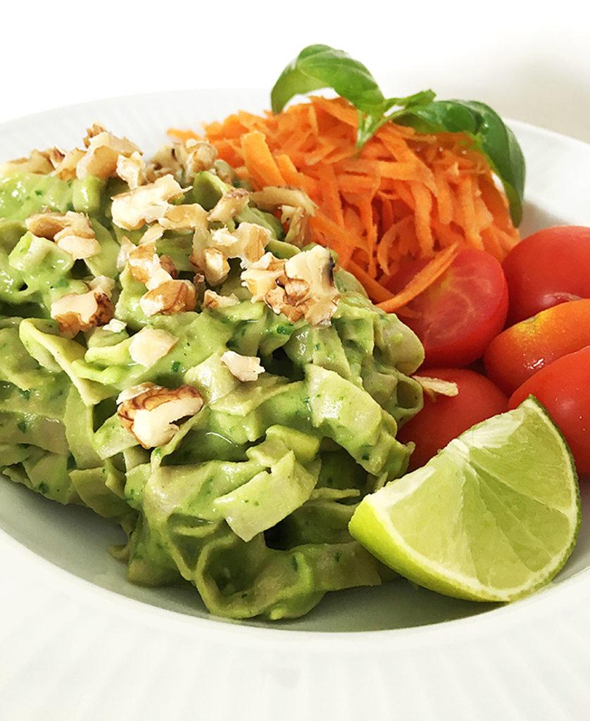 En portion vegansk och glutenfri krämig pastasås på avokado, spenat och bönpasta med riven morot och tomat toppad med hackade valnötter.