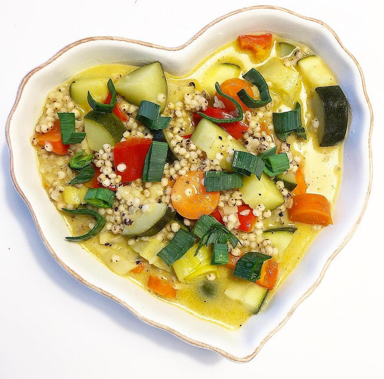 Foto på vegansk grönsaksragu med durrakorn serverat i ett hjärtformat vitt fat