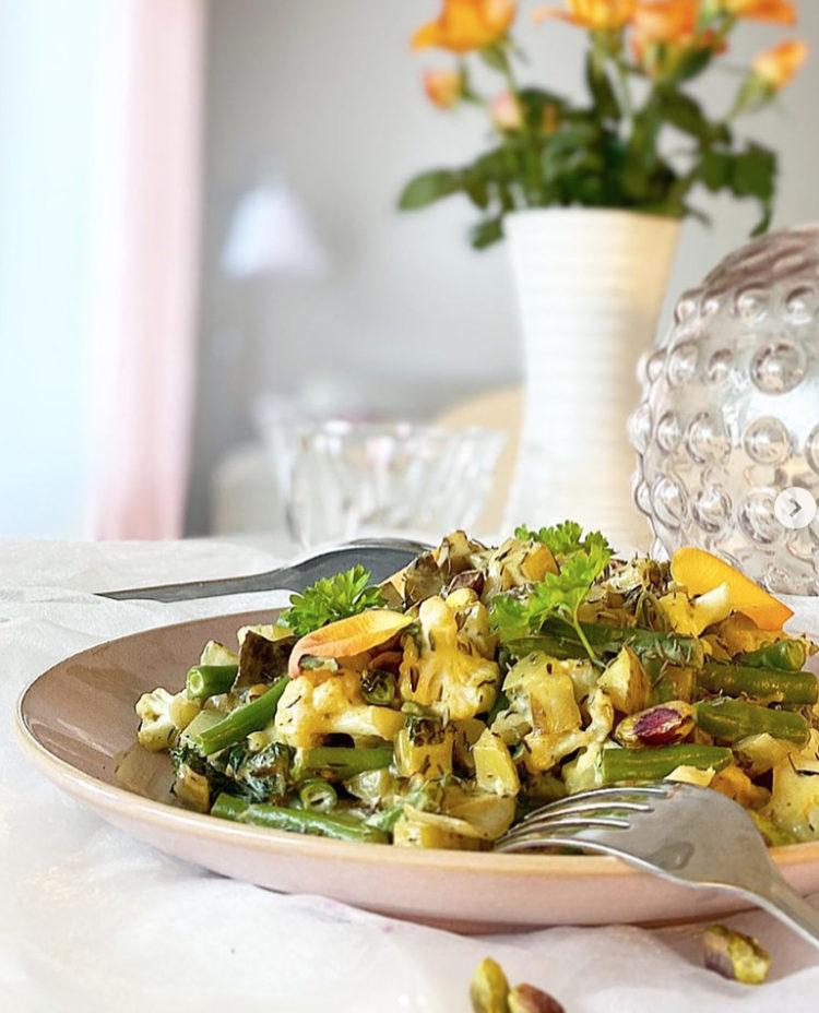 Ett fat med vegansk pytt i panna med trattkantareller med orangea blommor i bakgrunden.