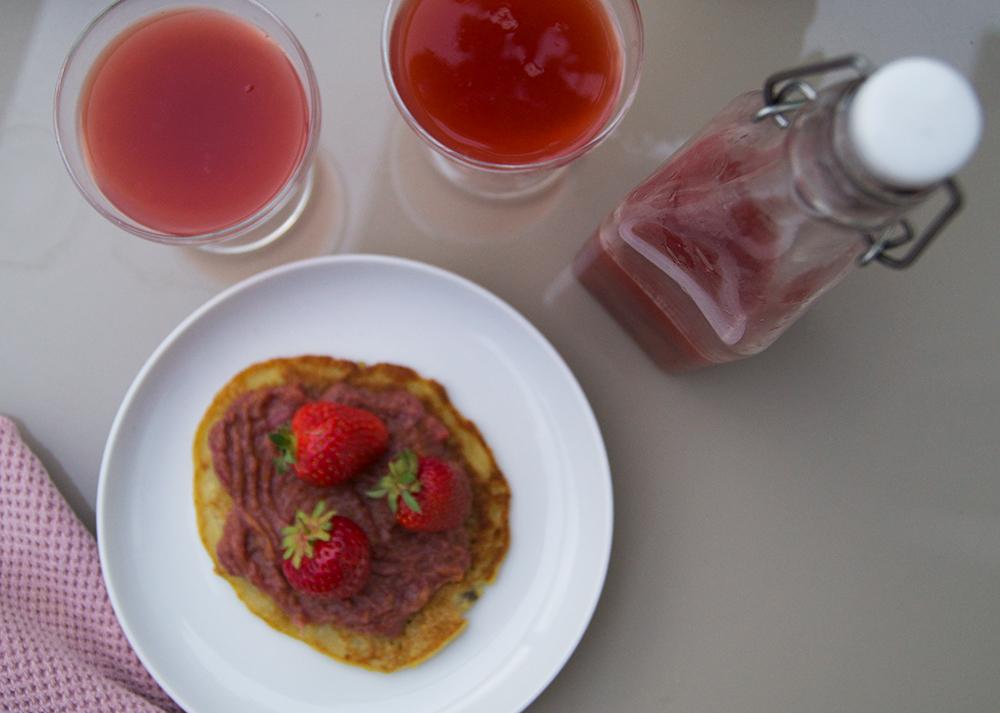 Foto på hemmagjord jordgubbs-hallon och rabarber saft och sylt i ett.
