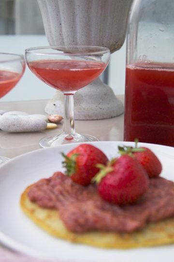 En plätt med jordgubbssylt och jordgubbssaft som står i bakgrunden.