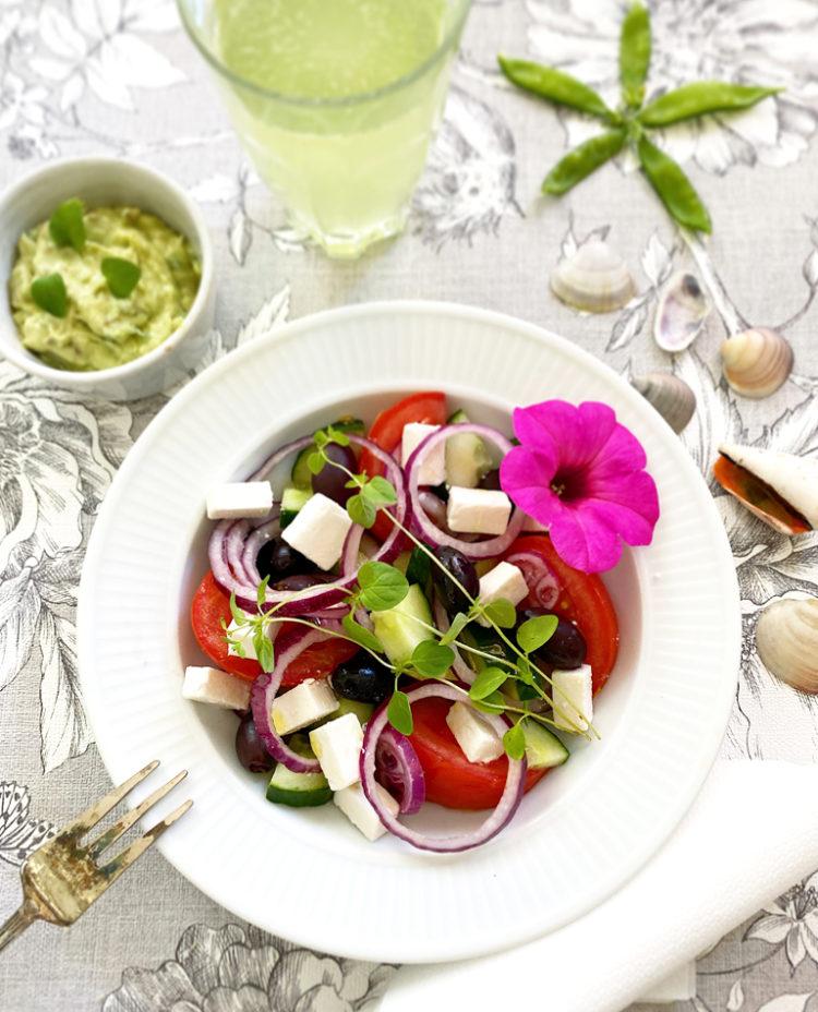 Ett fat med grekisk sallad med vegansk grekisk ost och avokado tzatziki serverat med gurkvatten och pyntat med en rosa blomma.
