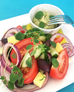 Foto på ett fat med vegansk grekisk sallad med avokado tzatziki.