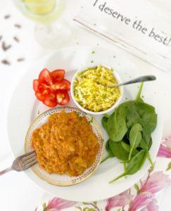 Ett fat med linsgryta med tomat, ingefära och spännande kryddor serverat med råriven blomkål med olivolja, en gnutta gurkmeja, flingsalt och rivet limeskal.