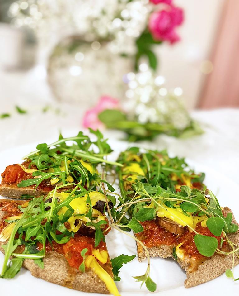Ett fat med glutenfri vegansk pizza toppad med ruccola och med en vas med rosa rosor i bakgrunden.
