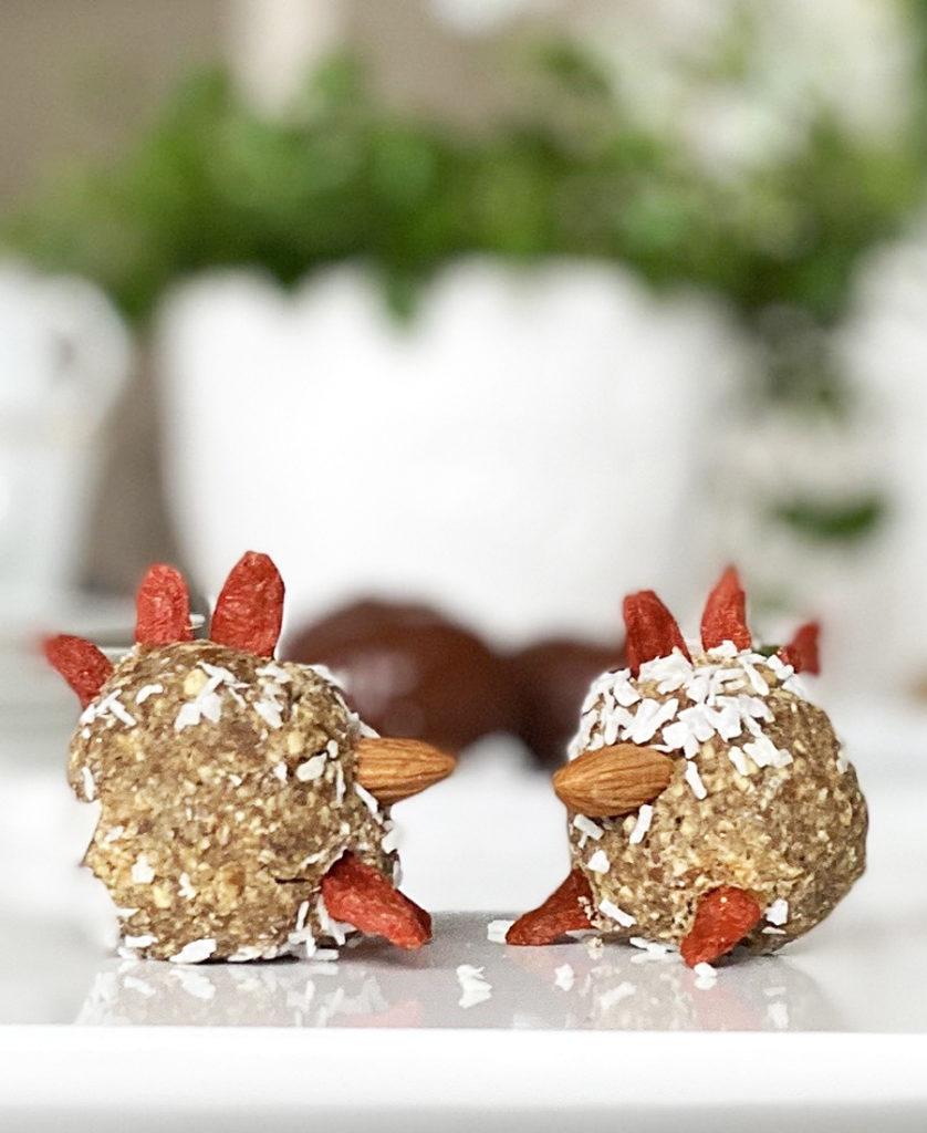 Veganska havrebollar smyckade som påsktuppar med hjälp av gojibär och mandlar.