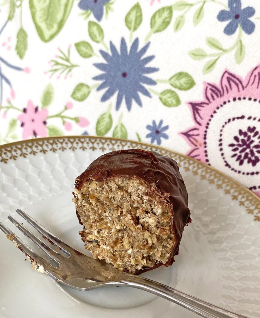 Vegansk havreboll som chägg (havreboll formad som ägg och doppade i mörk choklad som ligger på ett fat.