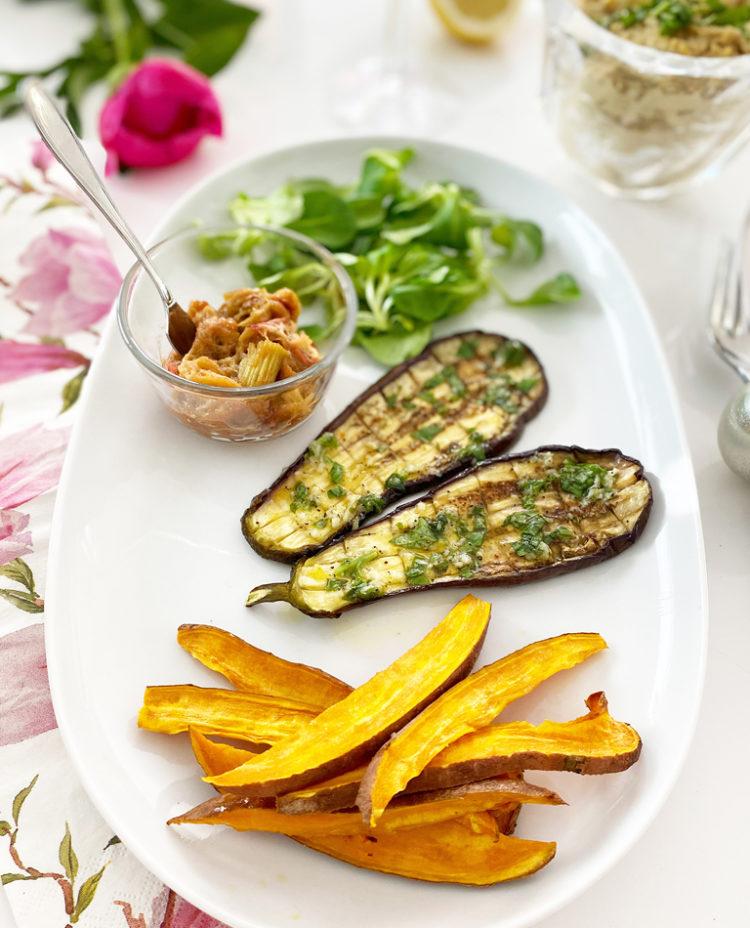 Ett fat med grillad aubergine med vitlök- och basilikadressing, sötpotatis och rabarberchutney.
