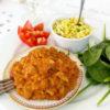 En tallrik med vegansk linsgryta serverat med råriven blomkål.
