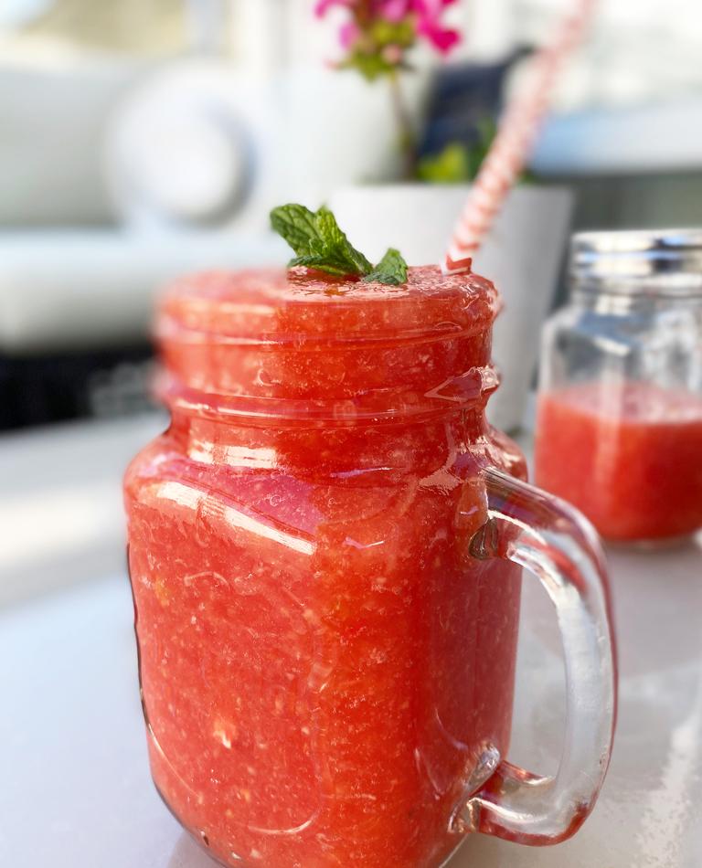 Ett glas med en röd melonsmoothie - raw vegan.