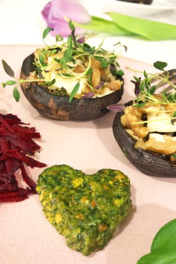 En tallrik med ugnsbakad portabello med valnötter, timjan och vegansk mozzarella serverat med hemmagjord vegansk pesto och riven rödbeta.