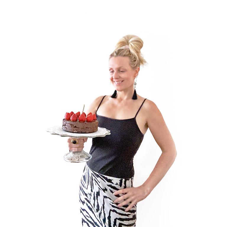 Yvonne Hedberg håller i en raw chokladtårta med jordgubbar.
