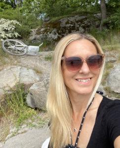 En kvinna i solglasögon som sitter på en klippa.