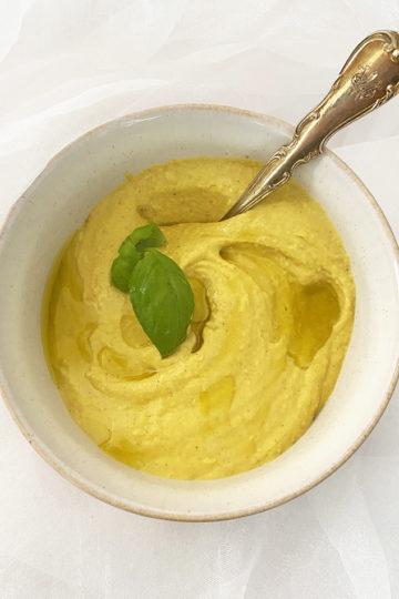 En skål med gul hummus med gurkmeja.