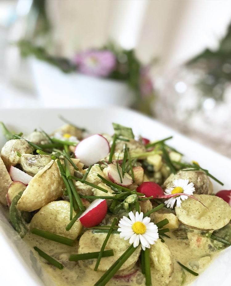 En skål med vegansk krämig potatissallad med curry och äpple toppad med tusensköna.