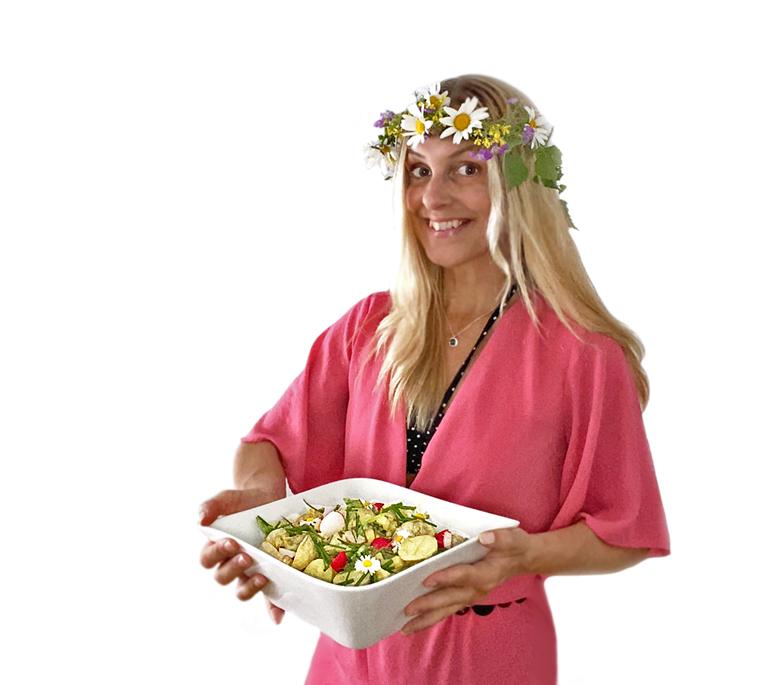 En kvinna i rosa kläder och midsommarkrans håller i en skål med vegansk potatissallad med curry och äpple.