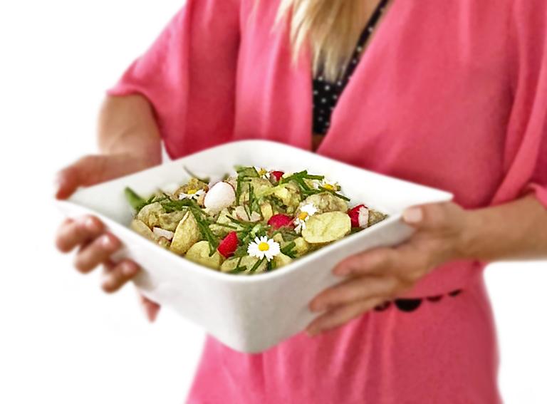En kvinna i rosa kläder håller i en skål med vegansk potatissallad med curry och äpple.