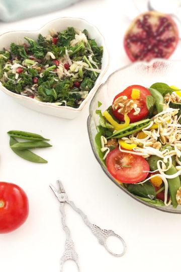 Två skålar med måltidssallader med bland annat spenat och grönkål.