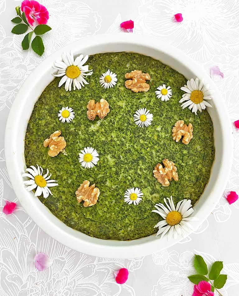 En vegansk spenatpaj dekorerad med valnötter och blommor.