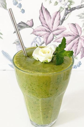 Ett glas med en vegansk grön selleri smoothie.