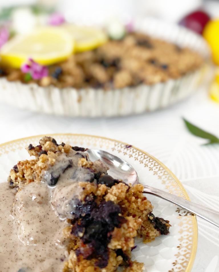 Ett fat med vegansk, glutenfri smulpaj med blåbär.