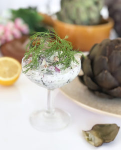 En skål med vegansk skagenröra toppad med dill och med kronärtskocka vid sidan av.