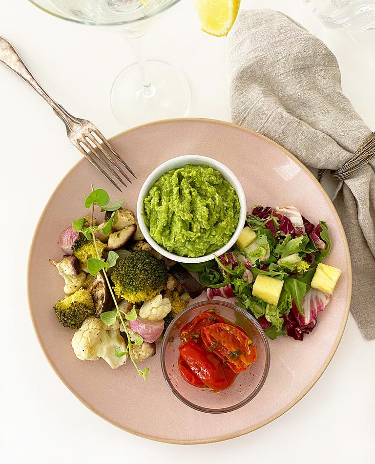 Ett fat med rostad broccolimix , ärtpuré och stekta röda tomater.
