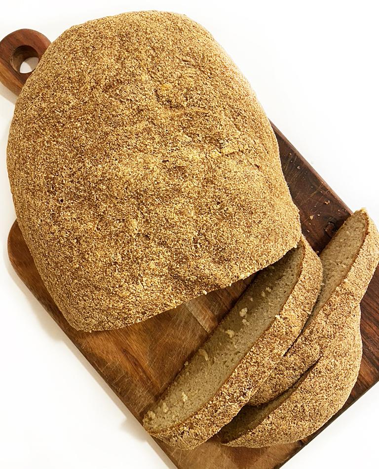 En uppskivat majs- och bovetelimpa ligger på en skärbräda.