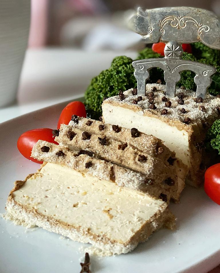 Griljerad tofu på ett fat med grönkål och tomater, garnerad med nejlika - glutenfri och vegansk.