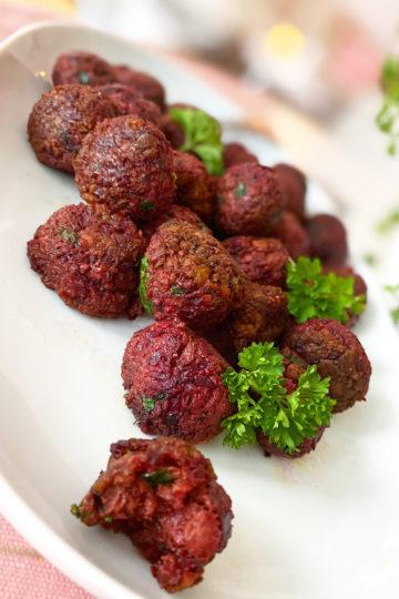Ett fat med glutenfria vegobullar med rödbeta och persilja.