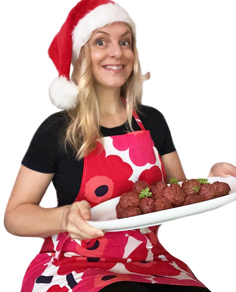 Yvonne i tomteluva och rödmönstrat förkläde håller upp ett fat med glutenfria vegobullar med rödbeta och persilja.