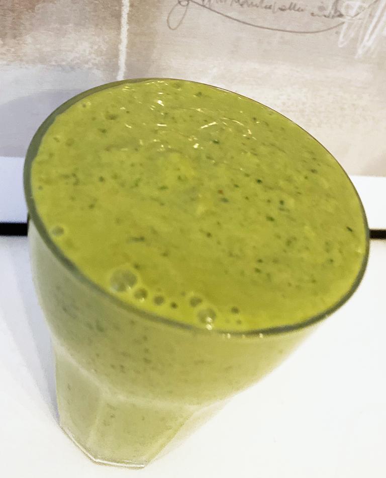 Ett glas med grön vegansk smoothie.